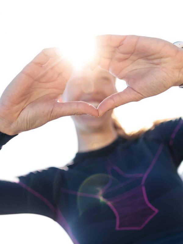Shot of sporty young woman making heart shape with hands while posing to camera on mountain.